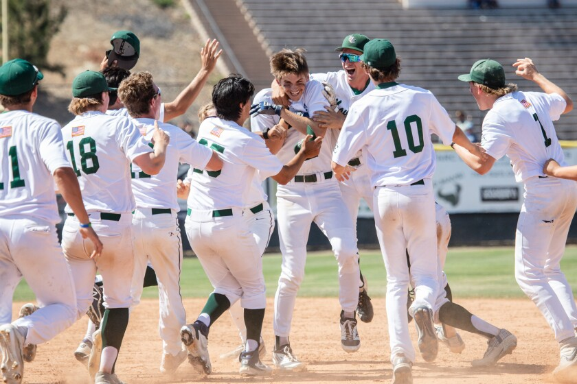 La Costa Canyon's Mark Prince (middle) is celebrated by his teammates after his walk-off hit against Long Beach Millikan.