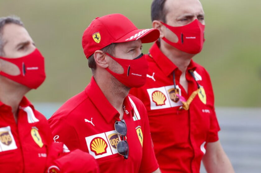 Ferrari driver Sebastian Vettel of Germany, center, inspects the track with his team at the Hungaroring racetrack in Mogyorod, Hungary, Thursday, July 16, 2020. The Hungarian Formula One Grand Prix race will take place on Sunday. (AP photo/Darko Bandic)