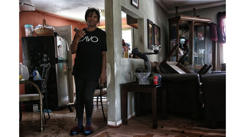 A day after flood waters receded, Yvonne Feruson-Smith assesses the damage to her home while talking
