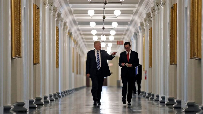 President Donald Trump walks with Treasury Secretary Steve Mnuchin as they look at portraits of the