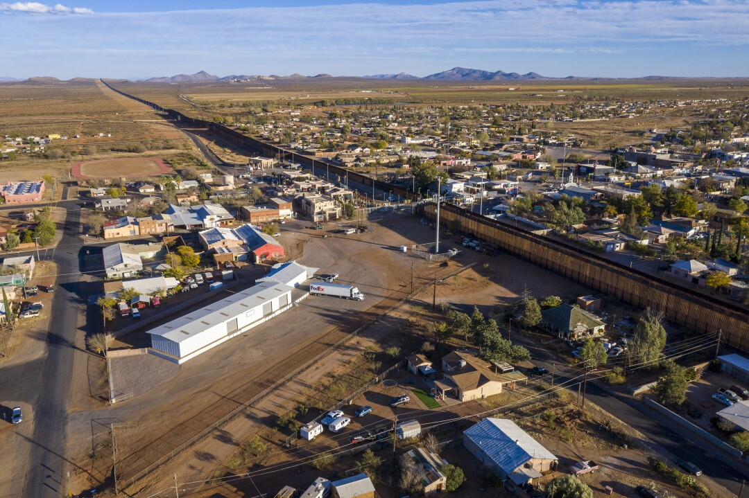 The Arizona town of Naco, left, and Sonora Mexico town of Naco, right, sit side by side, separated by the steel border wall.
