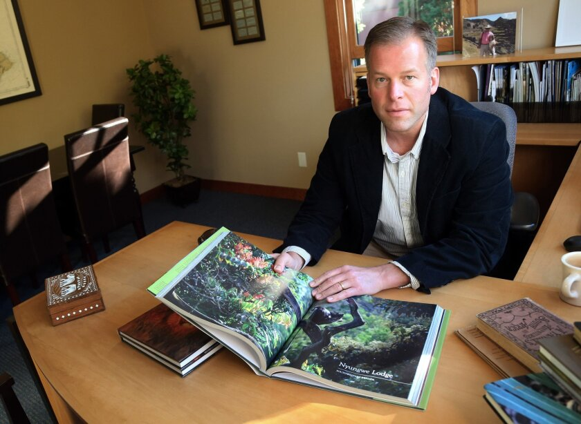 In this Oct. 21, 2014 photo, Craig Beal, owner of Travel Beyond, poses with books on Africa at his travel agency in Wayzata, Minn. Fear about the Ebola virus spreading is hurting businesses like Beal's. He has had three cancellations for safaris to places like Botswana and South Africa that are nine hours by plane from the countries with widespread outbreaks. (AP Photo/Jim Mone)