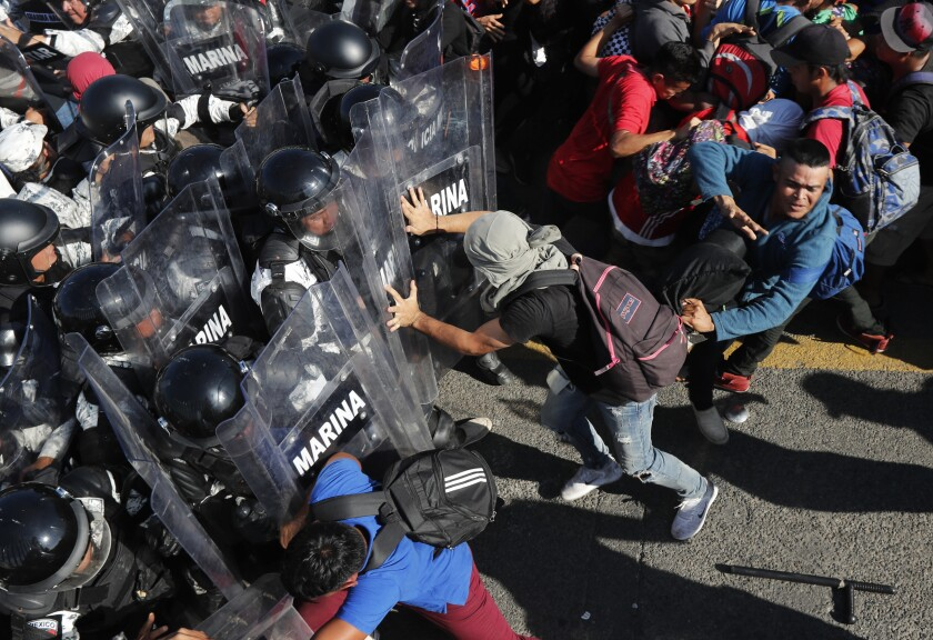 Migrants charge Mexican national guardsmen at the border crossing from Tecun Uman, Guatemala, into Mexico on Jan. 18, 2020.