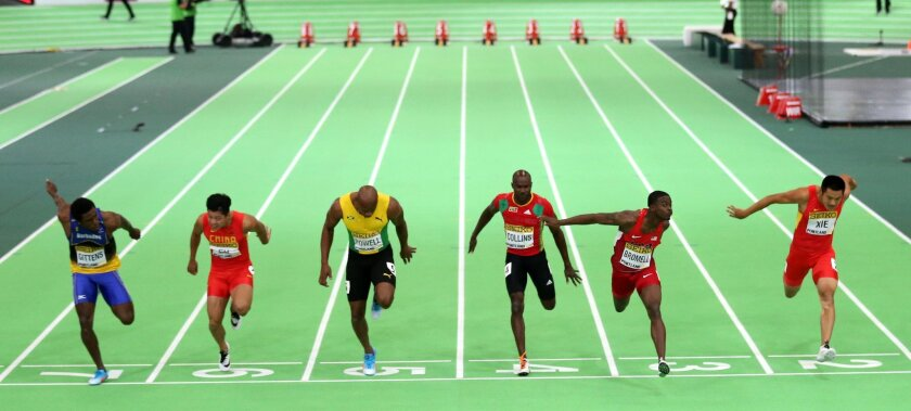 United States' Trayvon Bromell, second from right, crosses the finish line to win the men's 60-meter sprint final during the World Indoor Athletics Championships, Friday, March 18, 2016, in Portland, Ore. Jamaica's Asafa Powell, third from left, finished second, and Barbados' Ramon Gittens, left, finished third. (AP Photo/Rick Bowmer)