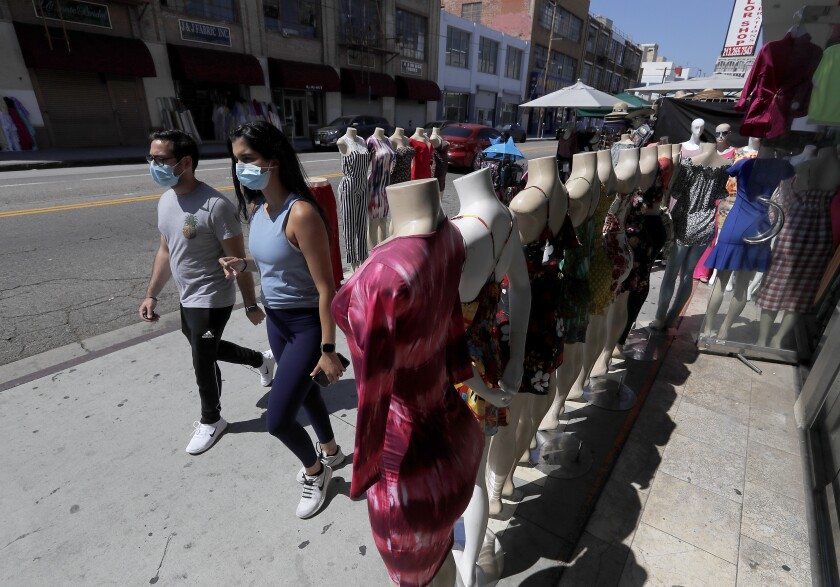 Shoppers wearing protective masks walk around the garment district on Thursday in downtown Los Angeles.