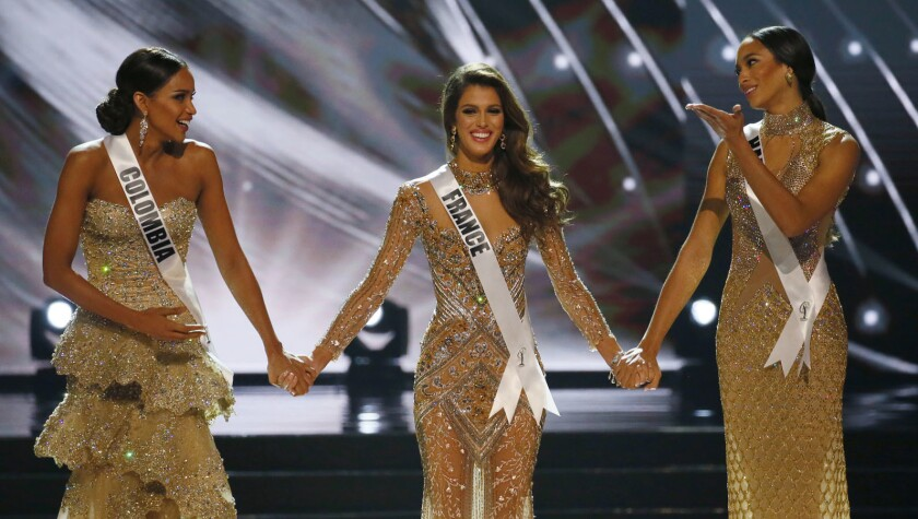 Miss France Iris Mittenaere, center, holds hands with Miss Colombia Andrea Tovar, left, and Miss Haiti Raquel Pelissier before the the Miss Universe is announced.