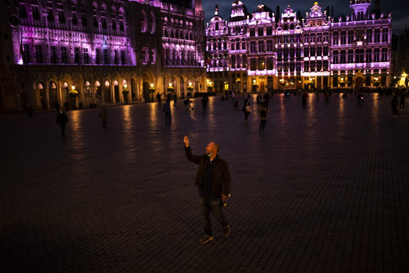 A passersby strolls and takes photographs on Grand Place during an autumn evening prior to the curfew in downtown Brussels, Friday, Oct. 23, 2020. In much of Europe, city squares and streets, be they wide, elegant boulevards like in Paris or cobblestoned alleys in Rome, serve as animated evening extensions of drawing rooms and living rooms. As Coronavirus restrictions once again put limitations on how we live and socialize, AP photographers across Europe delivered a snapshot of how Friday evening, the gateway to the weekend, looks and feels. (AP Photo/Francisco Seco)