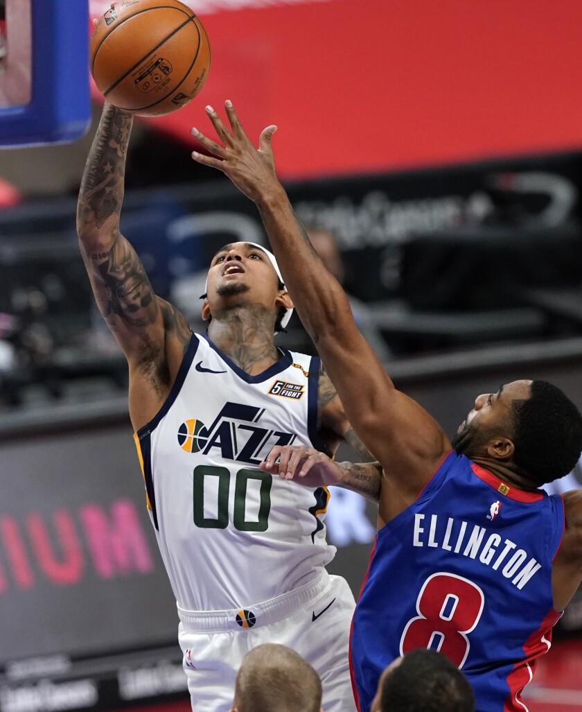 Detroit Pistons guard Wayne Ellington (8) attempts to block a shot by Utah Jazz guard Jordan Clarkson (00) during the first half of an NBA basketball game, Sunday, Jan. 10, 2021, in Detroit. (AP Photo/Carlos Osorio)