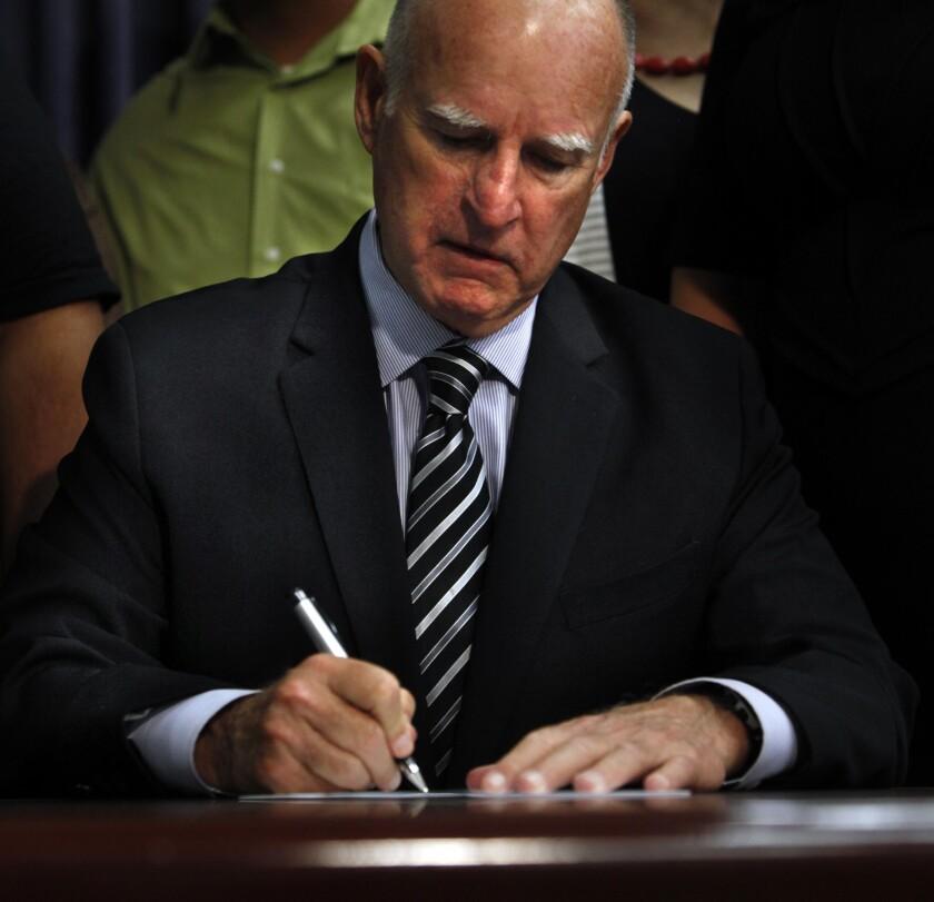 Gov. Jerry Brown signs legislation in Los Angeles on Sept. 10, 2014.