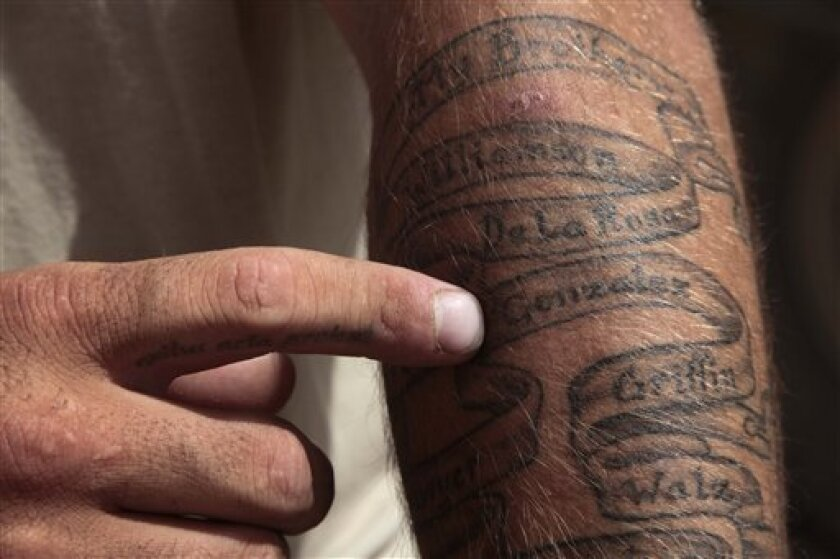 In this photo taken May 22, 2010, U.S. Army Sgt. Jacob Zimmerman, of Osh Kosh, Wis., talks about a tattoo he had done on his left arm while on leave in February. The tattoo features the 11 names of soldiers from 2nd Platoon, Charlie Company, who were killed in action during missions with1st Battalion, 17th Infantry Regiment of the 5th Stryker Brigade, 2nd Infantry Division in the Arghandab Valley of Kandahar Province in Afghanistan last fall. Twenty-two men in the U.S. Army's 1st Battalion, 17th Infantry Regiment of 800 died in a yearlong Afghan tour ending this summer. Most were killed last year in the Arghandab, a gateway to the southern city of Kandahar. About 70 were injured, all but two in bomb blasts. (AP Photo/Julie Jacobson)
