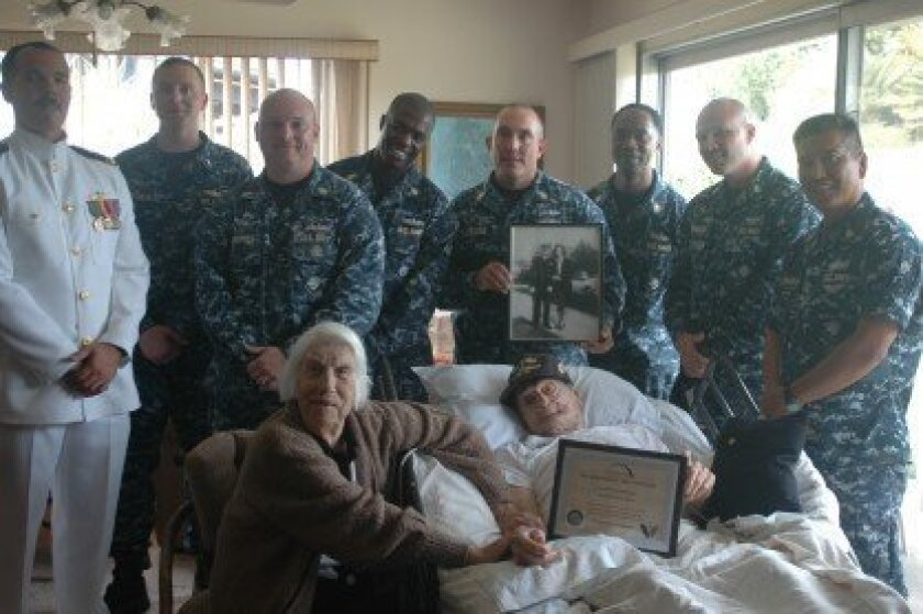 """Garnold poses with Wesley and local Navy Chiefs and Officers from PCU Jackson LCS6 who came to show their support for Garnold, who they referred to as """"The Chief."""" Garnold's wife of 70 years, Margaret, joins the crowd with an old photo of the couple in the background. Courtesy"""