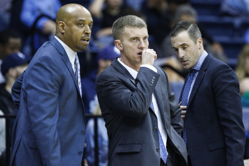 USD head coach Sam Scholl (center) speaks with assistant coaches Terrence Rencher and Chris Gerlufsen (right), who has accepted a job at Hawaii.