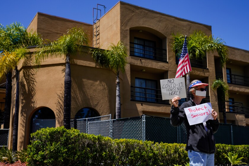 Protester Karen Litfin of Laguna Hills stands outside the Laguna Hills Inn, which the county is planning to use to house homeless people with the coronavirus.