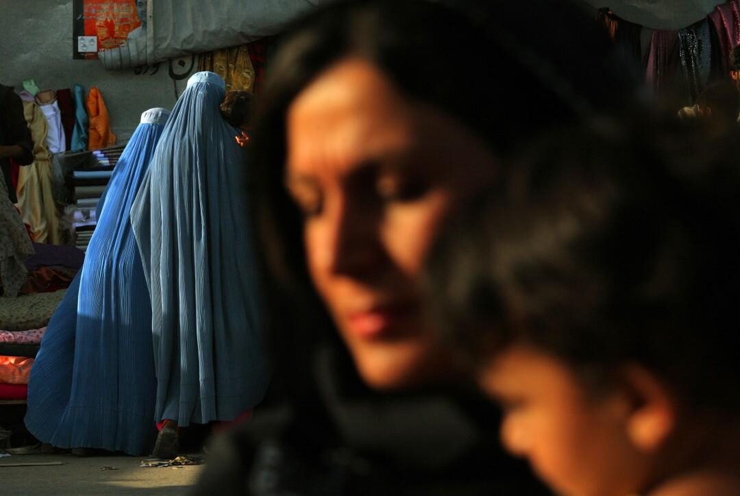 دو زن با برقع در حال قدم زدن در خارج از منزل هستند
