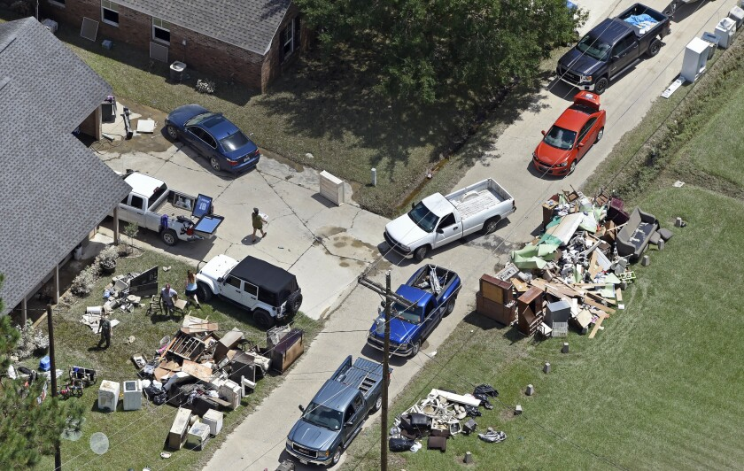 Residentes recogían escombros de sus casas para llevarlos a la basura cerca de la carretera 16 en Denham Springs, Louisiana, donde las personas comienzan el arduo proceso de recuperación de las más intensas inundaciones en la historia del estado. (Bill Feig/The Advocate via AP)