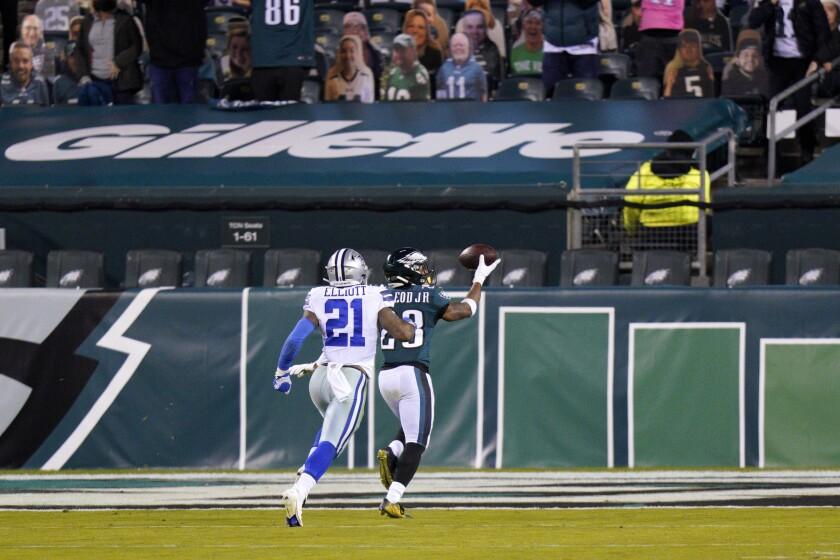 Philadelphia Eagles' Travis Fulgham (13) scores a touchdown past Dallas Cowboys' Ezekiel Elliott (21) after recovering a fumble during the second half of an NFL football game, Sunday, Nov. 1, 2020, in Philadelphia. (AP Photo/Chris Szagola)