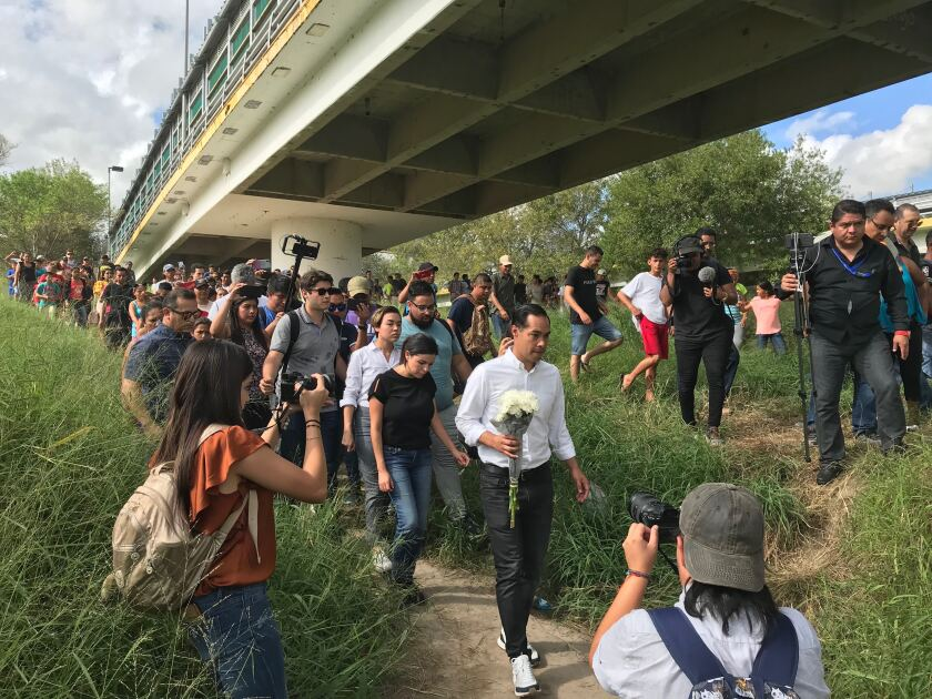 Julián Castro prepares to place flowers at crosses on the Rio Grande honoring migrants