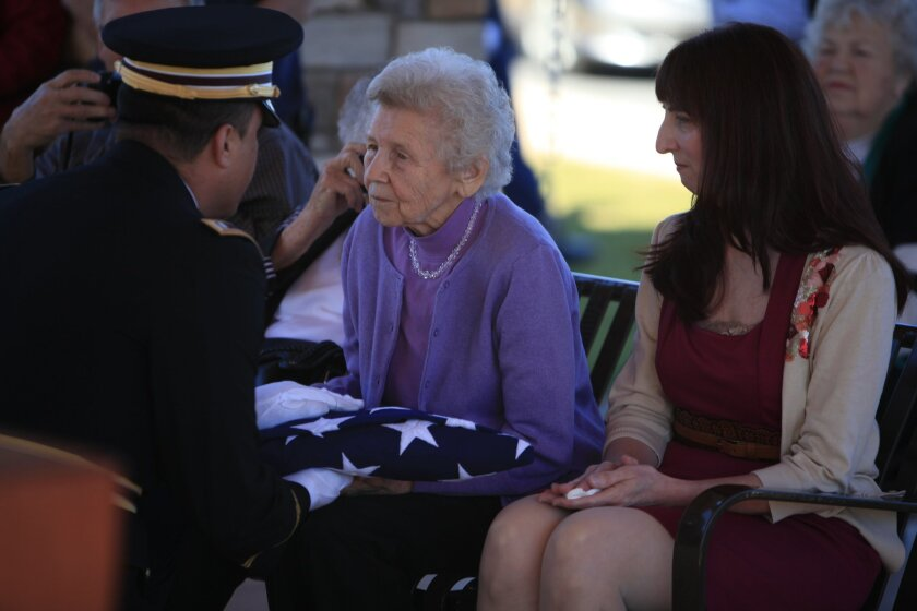 The reburial of Edwin Ware took place at Miramar's National Cemetary. Grand-daughter Bea Olivieri (left) accepted a memorial flag along side Ware's great grand-daughter, Sandra Ellis (right). U-T Photo by Christian Rodas