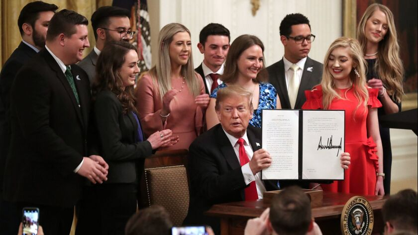 President Donald Trump holds up an executive order he signed protecting freedom of speech on college campuses during a ceremony in the East Room at the White House on March 21.