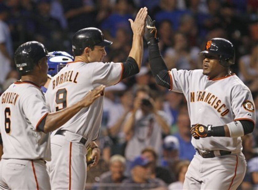 San Francisco Giants' Juan Uribe, right, celebrates with teammates Pat Burrell, center, and Jose Guillen after hitting a grand slam during the second inning of a baseball game against the Chicago Cubs, Thursday, Sept. 23, 2010, in Chicago. Uribe also hit a two-home run in the inning. (AP Photo/Nam Y. Huh)