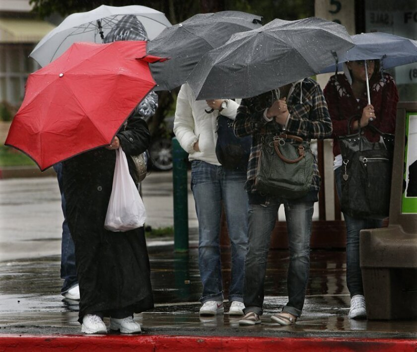 Bus riders are using umbrellas to protect themelves from the rain while waiting at Mission Boulevard and Felspar Street on Monday morning.