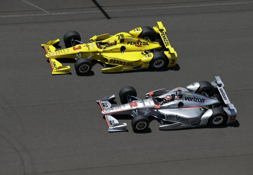 Penske teammates Helio Castroneves (3), of Brazil, and Will Power, of Australia, speed down the main straightway during a practice session for the Indianapolis 500 auto race at Indianapolis Motor Speedway in Indianapolis, Monday, May 23, 2016. (AP Photo/Michael Conroy)