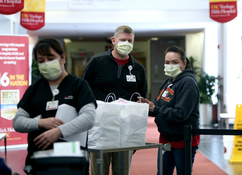 Chief Operating Officer Kenny Pawlek, center, and executive assistant Elen Borja, right, stand next to a Chinese food delivery from New Moon, at Verdugo Hills Hospital in Glendale on Tuesday, April 7, 2020.