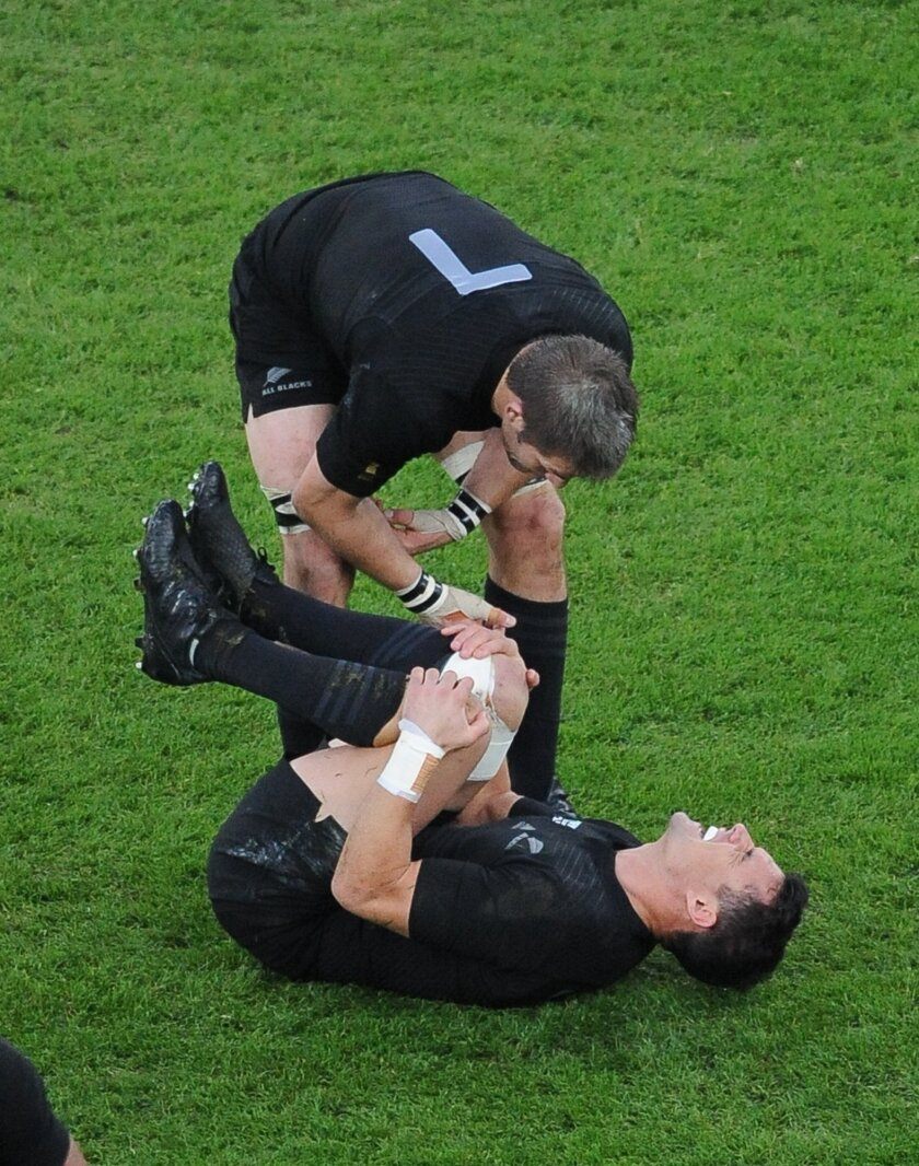New Zealand's Richie McCaw checks on teammate Dan Carter during their Rugby World Cup final match between New Zealand and Australia at Twickenham Stadium, London, Saturday, Oct. 31, 2015. (AP Photo/Rob Taggart)