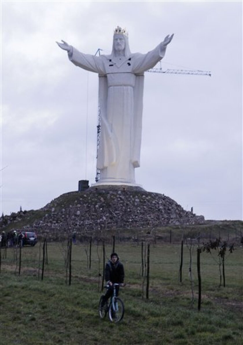 A cyclist passes a new monument to Jesus in Swiebodzin, Poland, on Saturday Nov. 6, 2010. A local priest built what his town members claim is now the largest statue of Jesus Christ in the world. (AP Photo/Czarek Sokolowski)