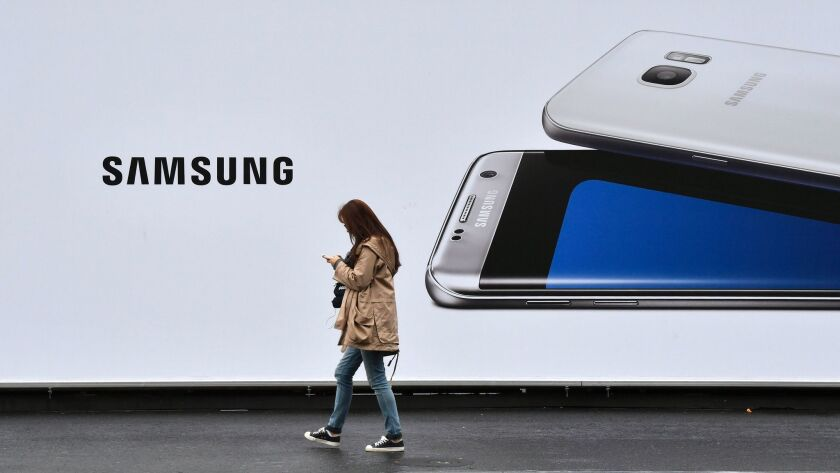 A woman checks her phone while passing by a billboard advertising a Samsung smartphone Oct. 11 in Berlin. The smartphone maker announced a total halt of production of the Galaxy Note 7 on Tuesday.
