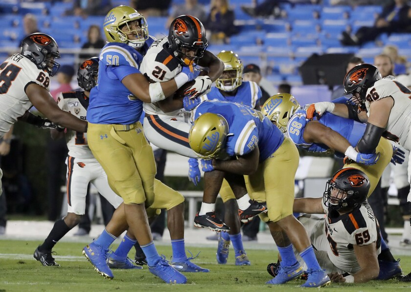UCLA's Tyler Manoa, left, and Winston Polite bring down Oregon State running back Nahshon Wright.