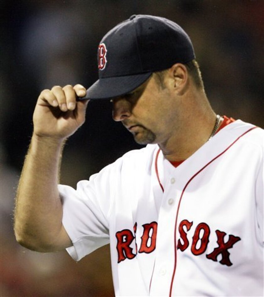 Boston Red Sox starter Tim Wakefield tips his cap to cheering fans after being taken out in the seventh inning against the Oakland Athletics in their baseball game at Fenway Park in Boston, Wednesday, July 8, 2009. (AP Photo/Elise Amendola)