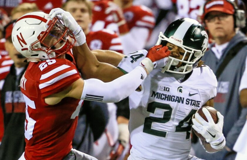 Michigan State running back Gerald Holmes (24) and Nebraska safety Nate Gerry (25) grab face masks during the first half of an NCAA college football game in Lincoln, Neb., Saturday, Nov. 7, 2015. (AP Photo/Nati Harnik)