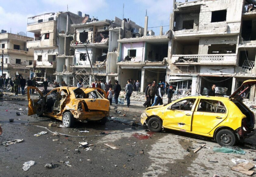 In this photo released by the Syrian official news agency SANA, Syrian citizens gather at the scene where two blasts exploded in the pro-government neighborhood of Zahraa, in Homs province, Syria, Sunday, Feb. 21, 2016. Two blasts in the central Syrian city of Homs killed more than a dozen people and injured many others in the latest wave of violence to hit the city in recent weeks, state TV said. (SANA via AP)