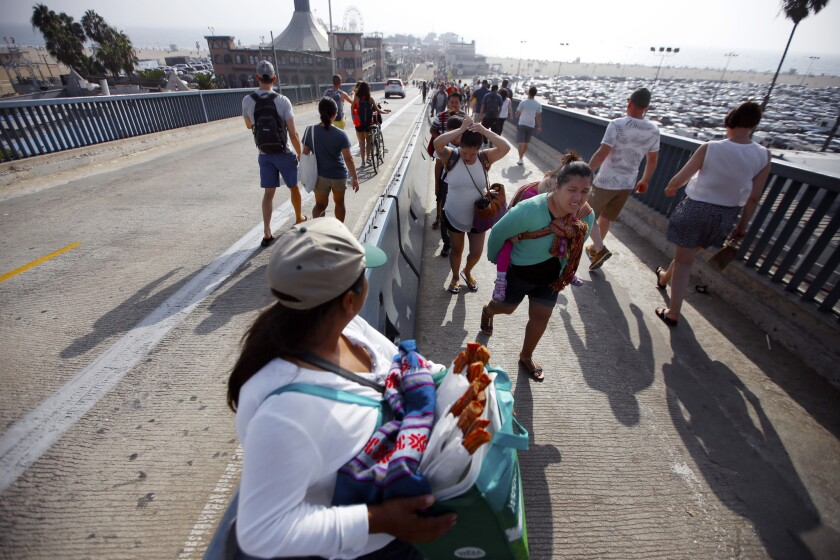 A street vendor sells churros out of a Whole Foods bag at the Santa Monica Pier last year.