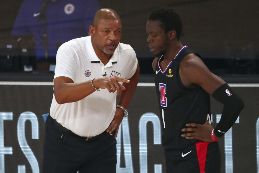 Clippers head coach Doc Rivers talks with guard Reggie Jackson.