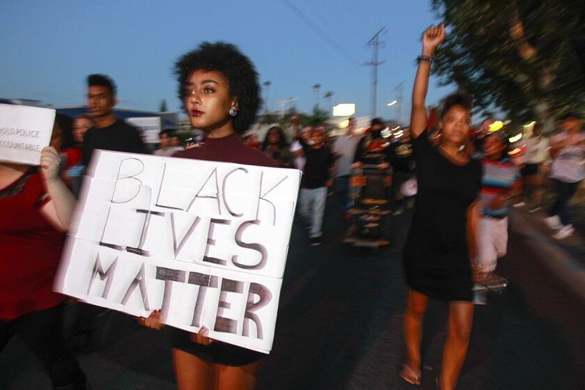 A woman carries a sign in a large crowd of people protesting the police shooting of Alfred Olango in El Cajon in 2016.