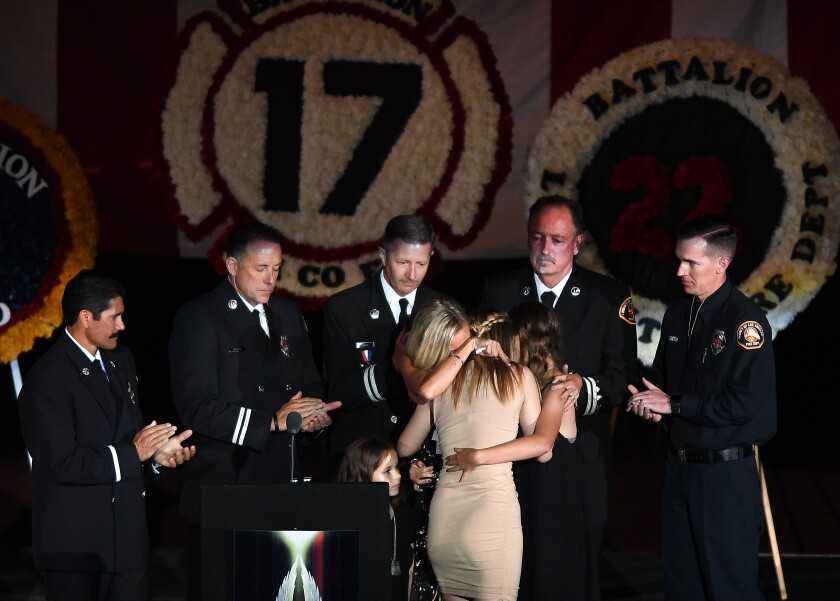 The wife and daughters of fallen L.A. County firefighter Tory Carlon hug during a memorial at the Forum