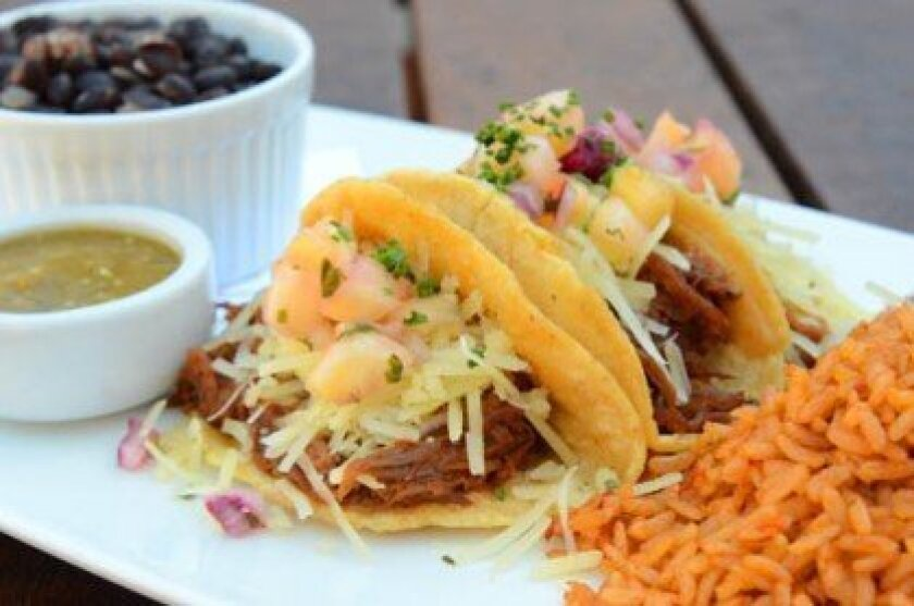 BBQ Duck Taco Trio is served with black beans and spanish brown rice.