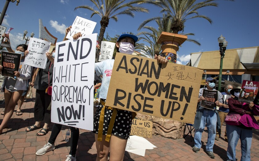 """A woman holds signs. One reads, """"End white supremacy now!"""""""