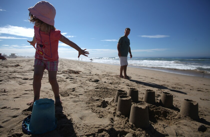 Haley Nelson, 3, and her father, Ryan Nelson, of Whittier, play in the sand at Huntington State Beach during Labor Day weekend in 2013. U.S. travelers are expected to spend $13.5 billion during this holiday weekend.