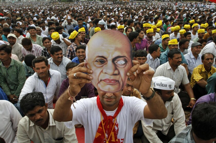 A Patidar, or member of Patel community, holds a mask of Indian freedom fighter and first Home Minister of Independent India Sardar Vallabhbhai Patel as he participates in a rally in Ahmadabad, India, Tuesday, Aug. 25, 2015.