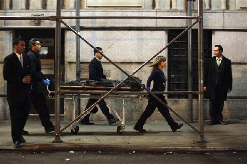 Hotel security and police officers stand guard as members of the Medical Examiners Office remove a body from the Peninsula Hotel Friday, Feb. 5, 2010 in New York. (AP Photo/Mary Altaffer)