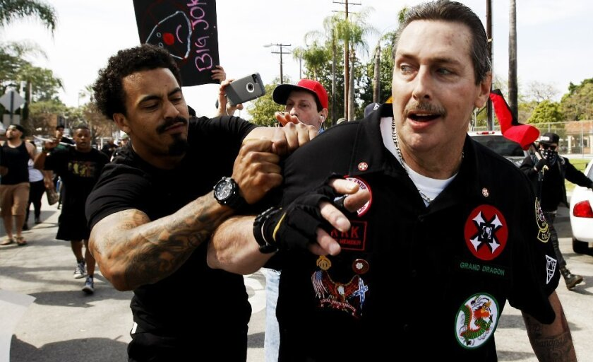 William Hagen, right, at a Ku Klux Klan rally in Anaheim, was arrested and charged with assault with a deadly weapon in North Carolina.