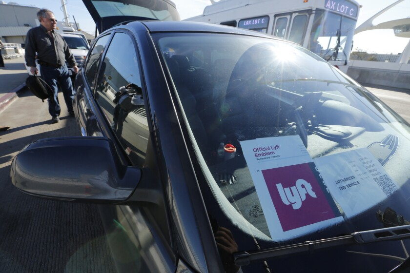 Lyft and GM are starting a short-term car rental program for Lyft drivers. Above, a Lyft car at Los Angeles International Airport.