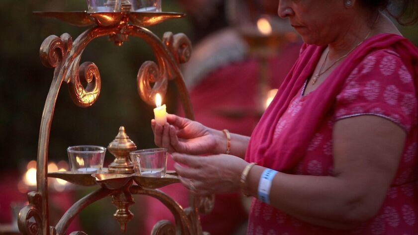 Suneela Kapila lights brass lamps at dusk for the 8th Annual Festival of Lights-Diwali Celebrations at Balboa Park in 2015.