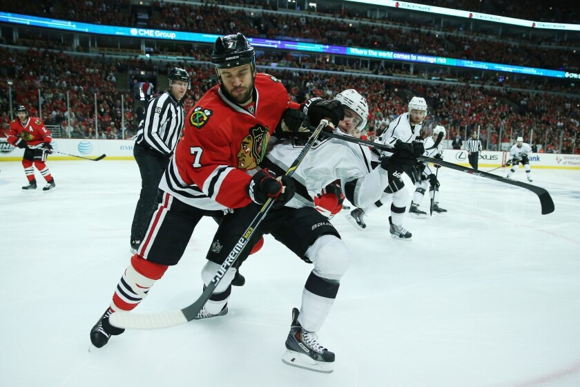 Blackhawks defenseman Brent Seabrook and Kings forward Tanner Pearson battle for position and the puck as they head to the corner in the first period.