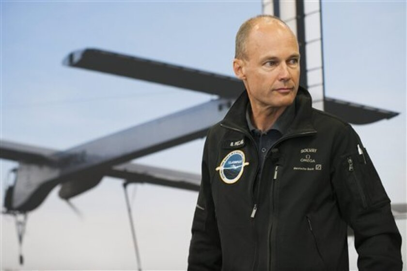 """Solar Impulse co-founder and chairman Bertrand Piccard speaks about the telemetry transceiver which does not work on the solar powered Aircraft """"Solar Impulse"""" (HB-SIA prototype) after the first attempt of a night flight fueled by the sun was postponed at the military airport in Payerne, Switzerland, Thursday, July 1st, 2010. The Swiss team planning to circle the globe in a solar-powered plane has postponed a 24-hour test flight because of this equipment problem. Bertrand Piccard, co-founder of the Solar Impulse team, says he cannot say when the next attempt will be made. But he says the test flight has to happen before the beginning of August because after that the days will be too short to charge the plane's batteries to last through the night. Pilot Andre Borschberg says the problem is down to a German-built piece of measurement equipment. (AP Photo/Keystone/Laurent Gillieron)"""