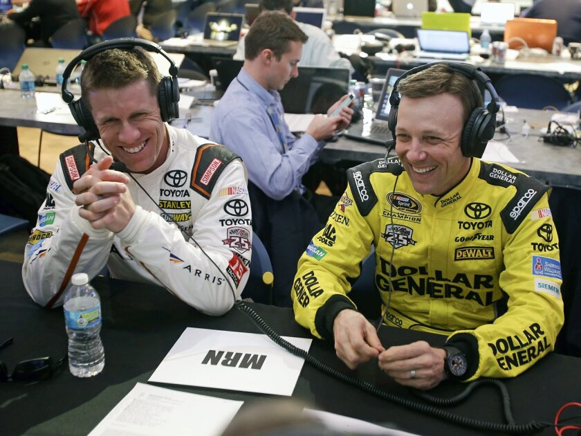 Drivers Carl Edwards, left, and Matt Kenseth share a laugh during a radio interview at NASCAR media day at Daytona International Speedway, Tuesday, Feb. 16, 2016, in Daytona Beach, Fla. (AP Photo/John Raoux)