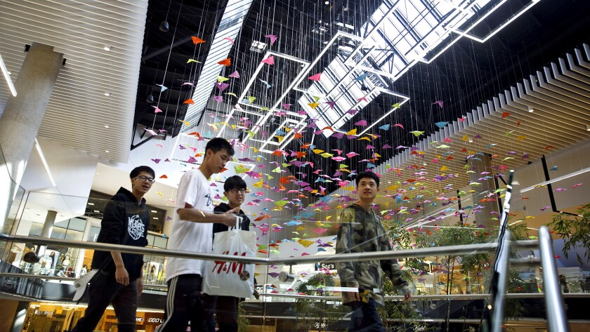 People walk past paper butterflies hanging inside the Westfield Santa Anita shopping mall on Friday,